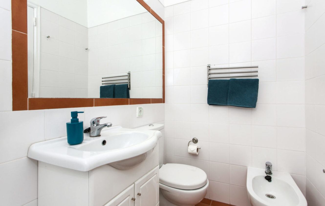 Bathroom with a big wall mirror, sink, toilet and bidet at the apartment in Algés Portugal