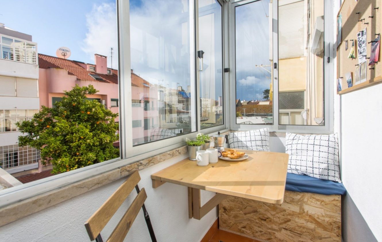 Closed balcony and breakfast nook with an orange tree view at the apartment in Algés Portugal
