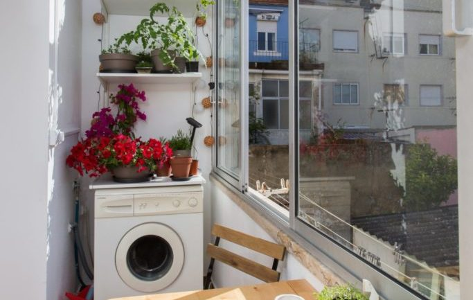 Closed balcony and breakfast nook with home garden and washing machine at the apartment in Algés Portugal