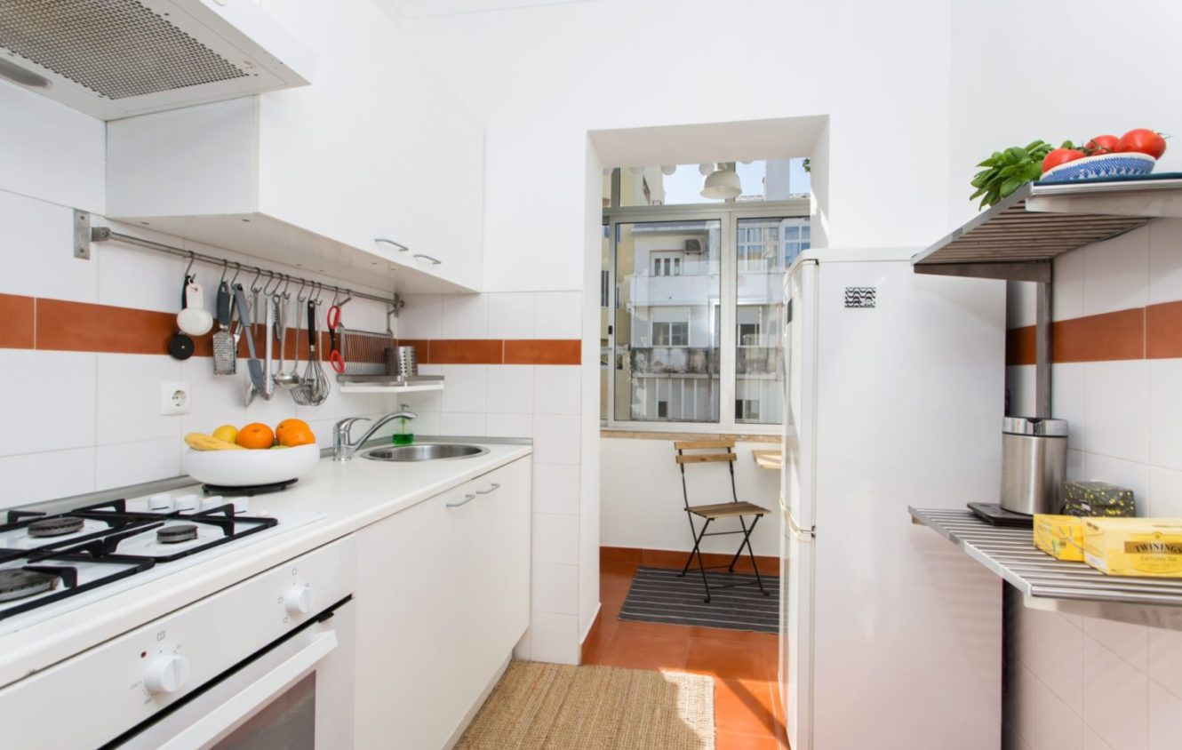 Fully equipped kitchen with the entrance to the closed balcony at the apartment in Algés Portugal